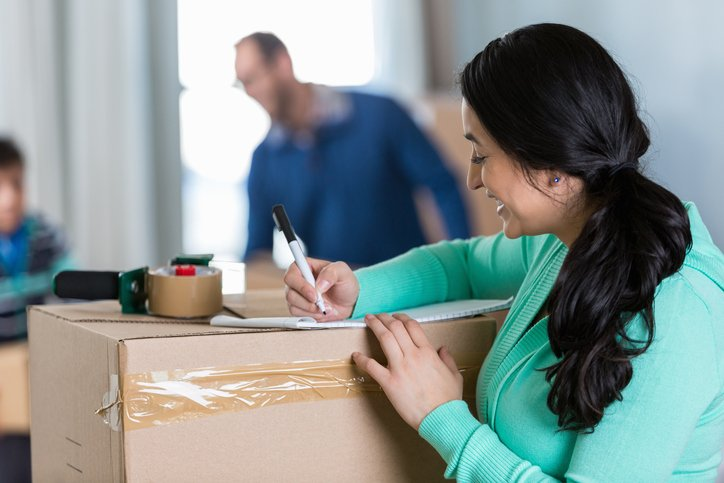 woman labeling boxes and checking inventory on moving day