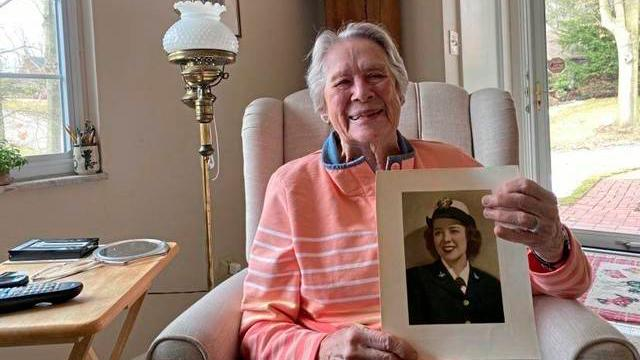 Julia Parsons with a photo of herself from her days of service in the U.S. Navy during World War II