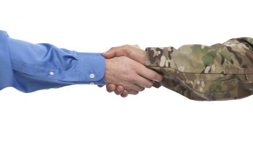 corporate hand shaking military hand